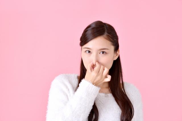 鼻をつまむ女性